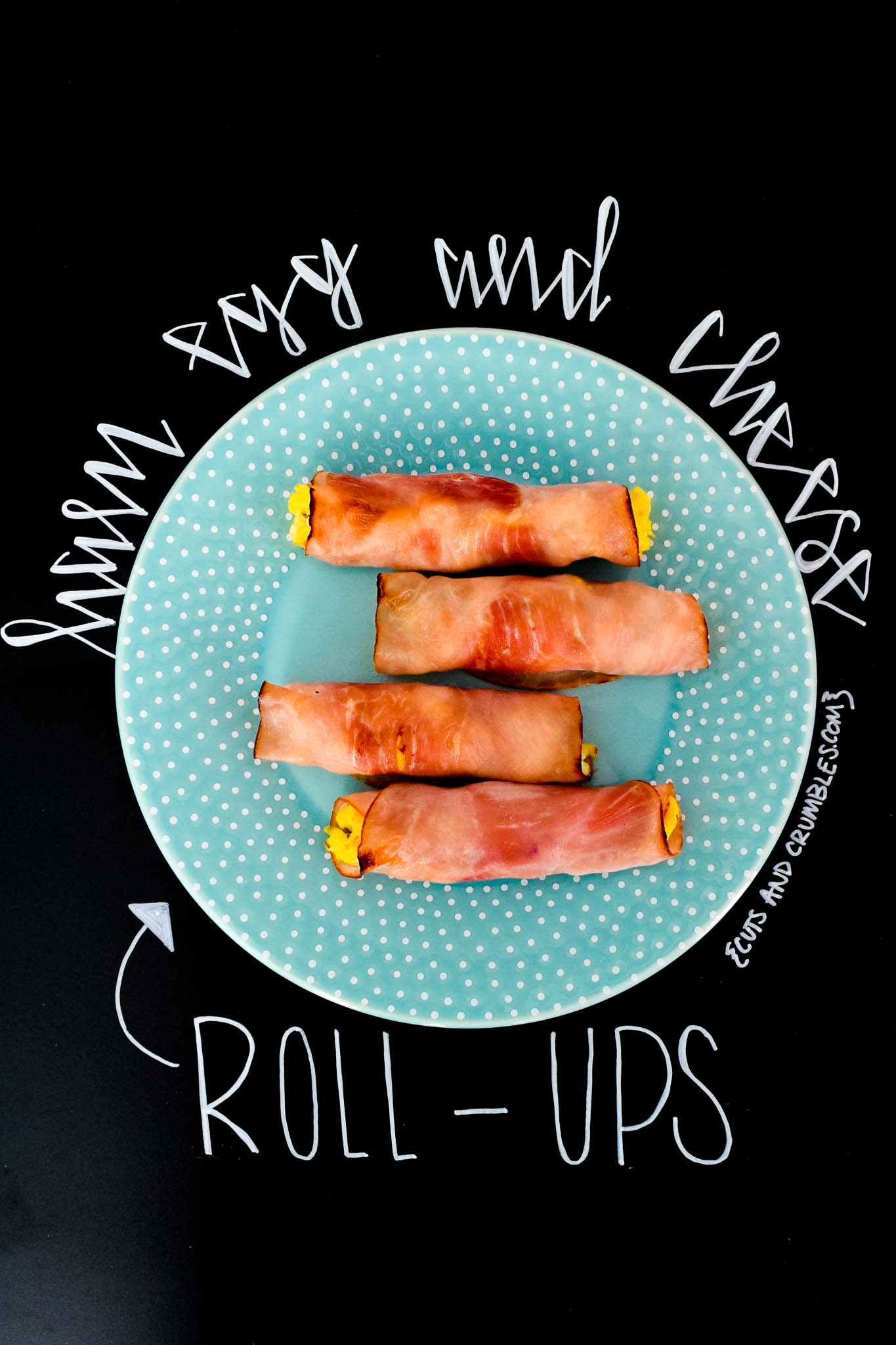 Ham Egg and Cheese Roll-Ups on blue plate with title written on chalkboard