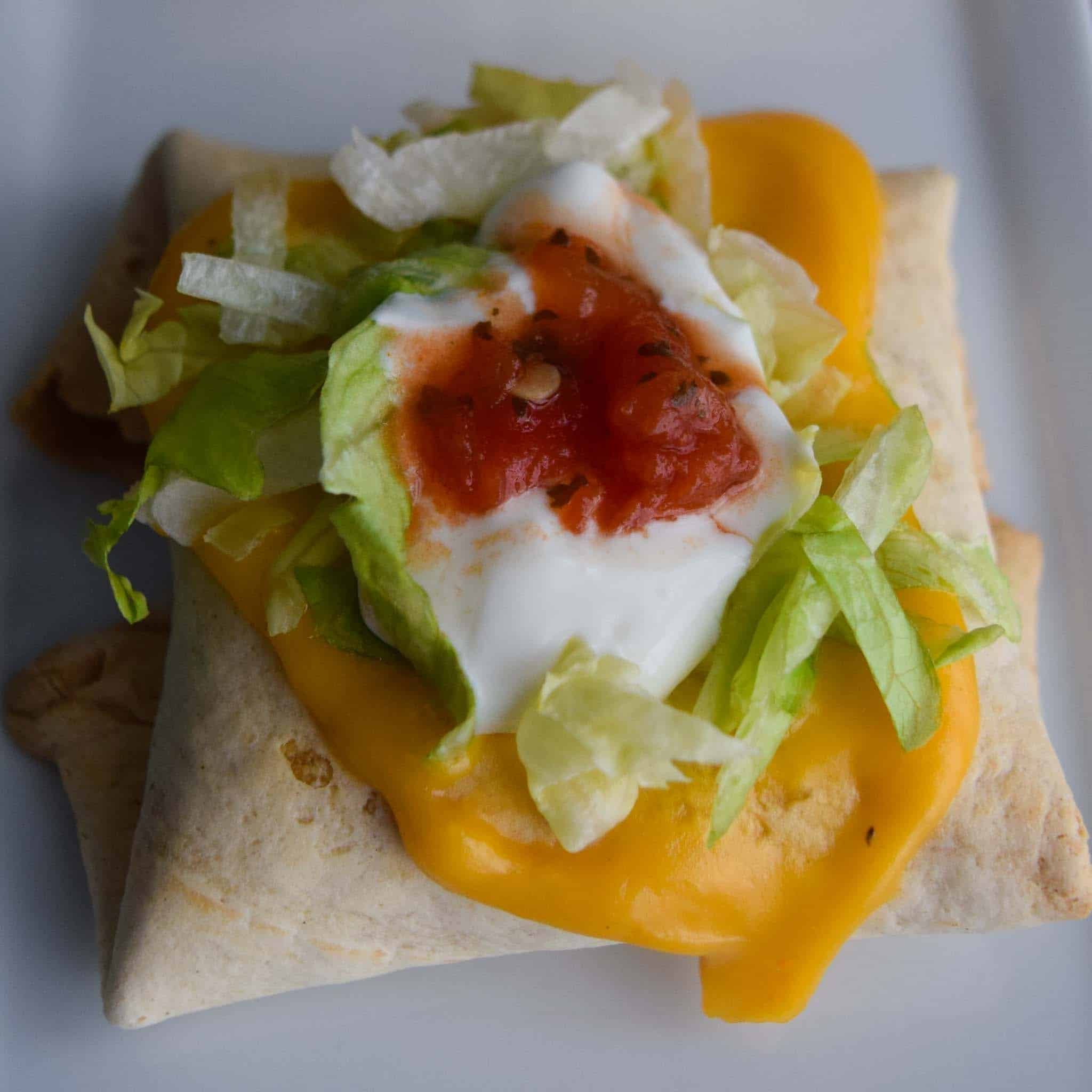 Baked Chimichangas with Guilt-Free Cheesy Sauce topped with lettuce sour cream and salsa close up view