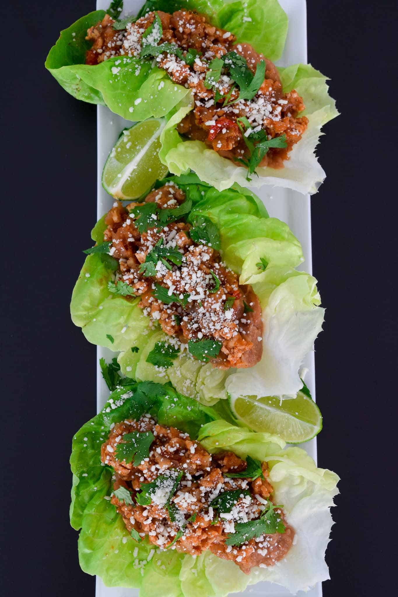 Chicken Tacos in Lettuce Wraps on white platter ready to be served overhead shot