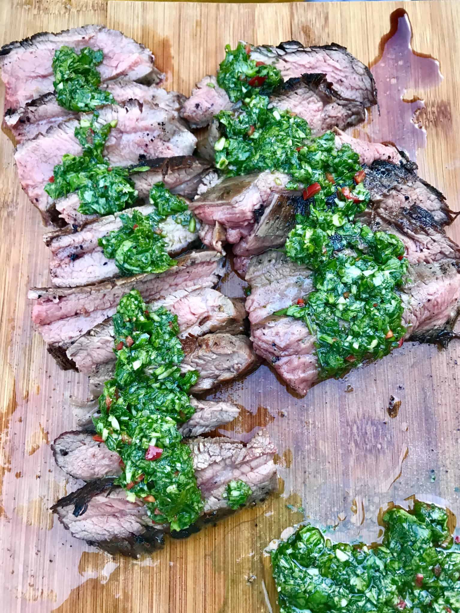 Caveman Style Flank Steak sliced on wooden cutting board topped with chimichurri sauce overhead shot