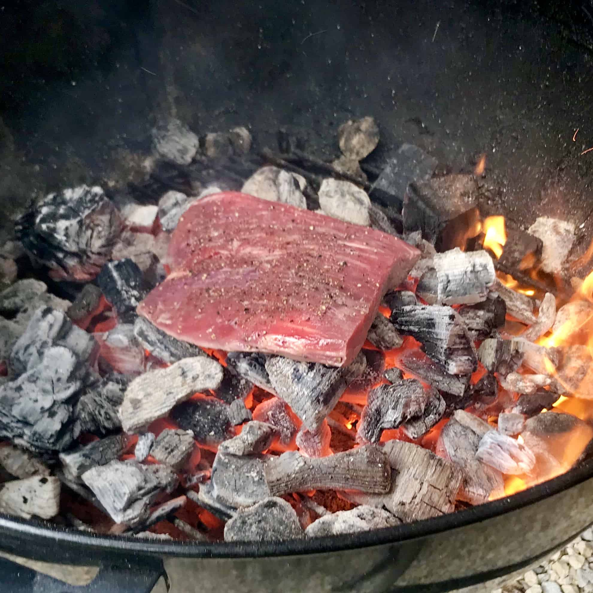 Raw steak being cooked directly on hot coals close up view