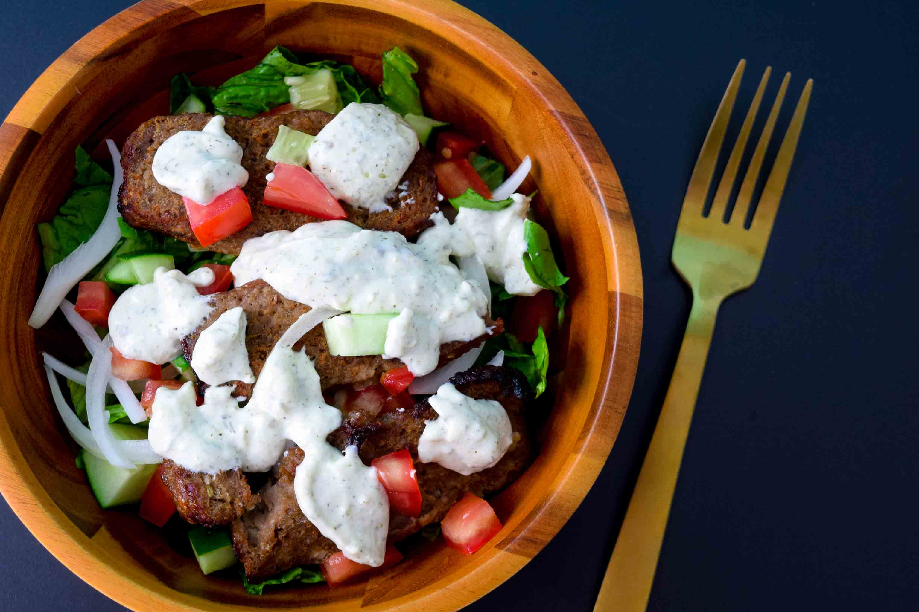 Gyro meat in salad bowl covered in tzatziki sauce on black background