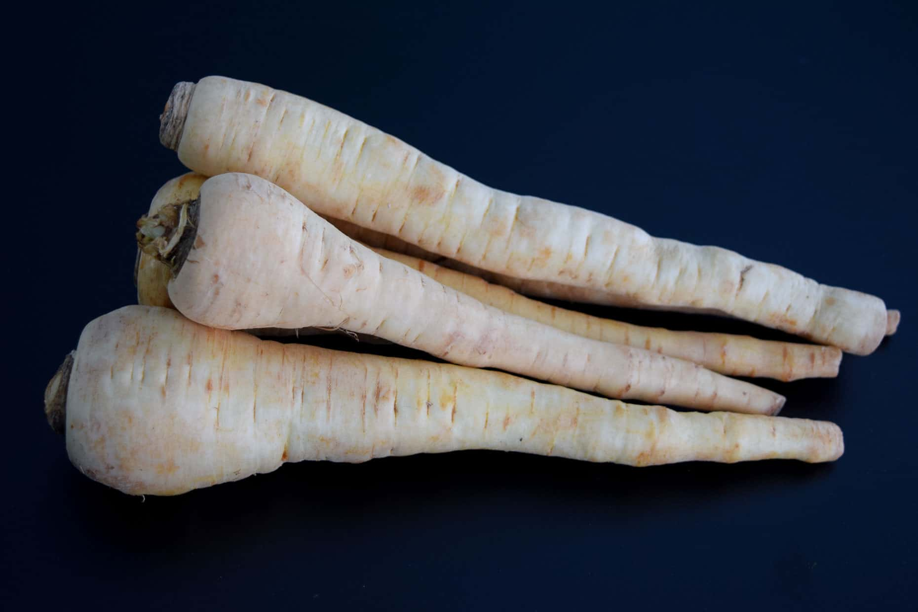Parsnips on black background
