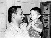 With his father and a mischievous smile