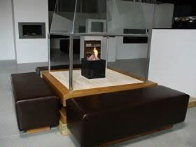 square fire table with stone top leather seats and a glass canopy - as about our bespoke fireplaces.