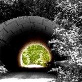 Hier sieht man einen Tunnel der fast gänzlich Schwarz wird in der Mitte, bis es hinten Licht am Tunnelende gibt. Vor dem Tunnel ist alles farblos und erst nach dieser Dunkelheit findet man Licht und Farben.