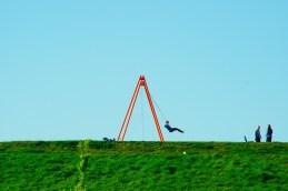 Schaukelndes Kind auf einem Hügel