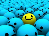 A single yellow smiley face in a sea of blue frowny faces
