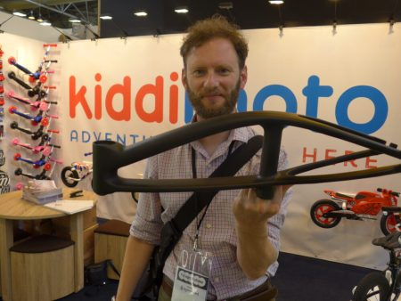 Kiddimoto Karbon balance bike being lifted by one finger
