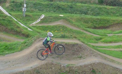 Practising front wheel lifts on an Islabikes Creig 24 at The Track Bike Park, Portreath, Redruth, Cornwall