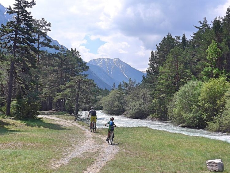 Family cycling in the Vallée de la Clarée in the French Alps - trail by the river Clarée