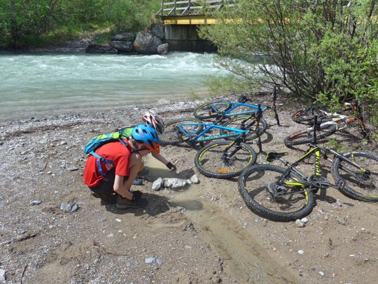 Family cycling in the Vallée de la Clarée in the French Alps - perfect place for the children to do a bit of dam building