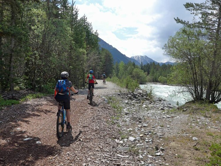 Family cycling in the Vallée de la Clarée in the French Alps - bikes following the river Clarée