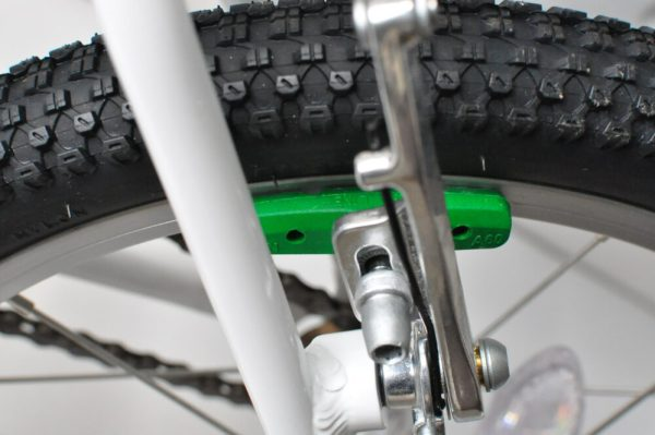 "Green brake blocks on the Woom 3 16"" wheel kids bike"