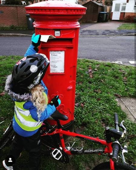 Girls on bicycles - posting a letter to Santa by bike