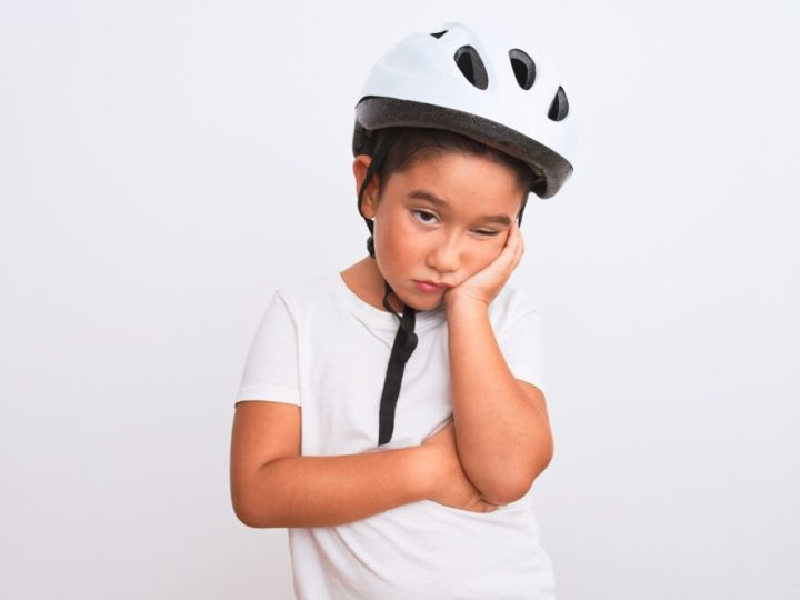 Boy wearing white cycling helmet not wanting to ride his bike