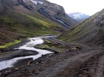 Dalgång i Islands inland med grusväg.