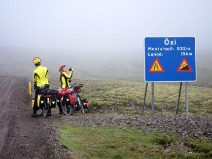 Dimma med två cyklister vid vägskylt om brant nerförsbacke.