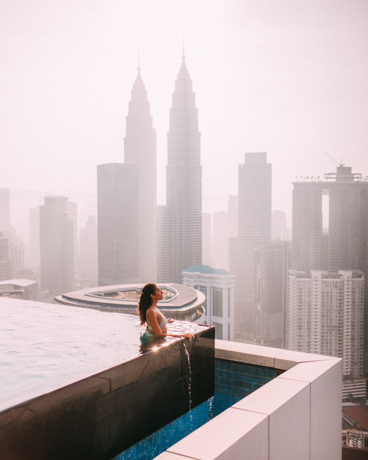 women swimming in a swimming pool watching the petrona towers
