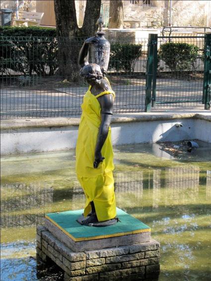"""Exposition """"Parc des expositions """" Stratue de la fontaine au centre du parc de Caveirac, portant une robe sur mesure en serpillère jaune fluo sur un socle en éponges."""