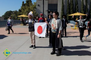 Students dressed as characters from Mario Bros. with flag of Japan