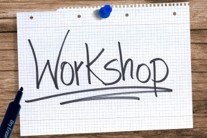 "Paper tacked to the desk with the word ""Workshop"" written on it and underlined, along with a pen next to the paper"