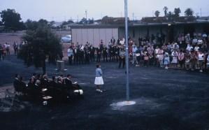 Speaker addressing students outside near flagpole