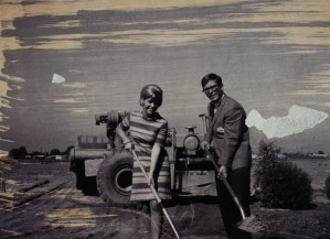 Two people with shovels in front of tractor