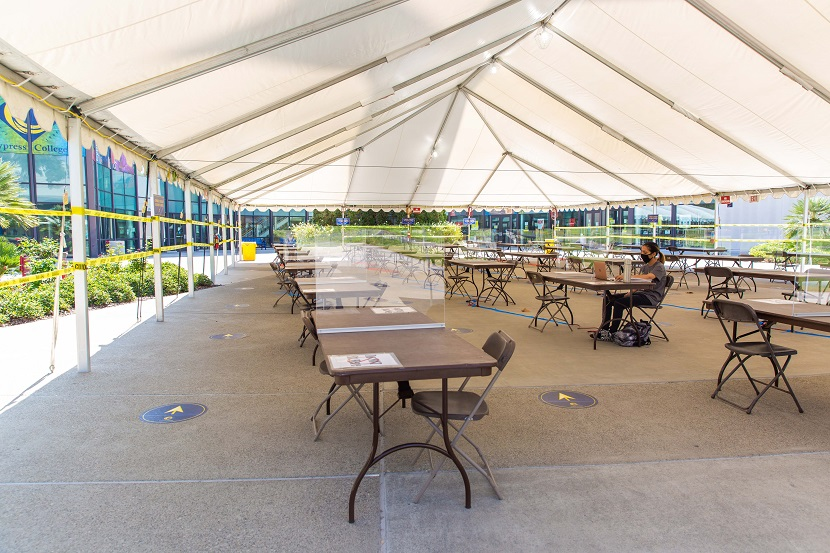 Tent with tables and chairs and a student studying