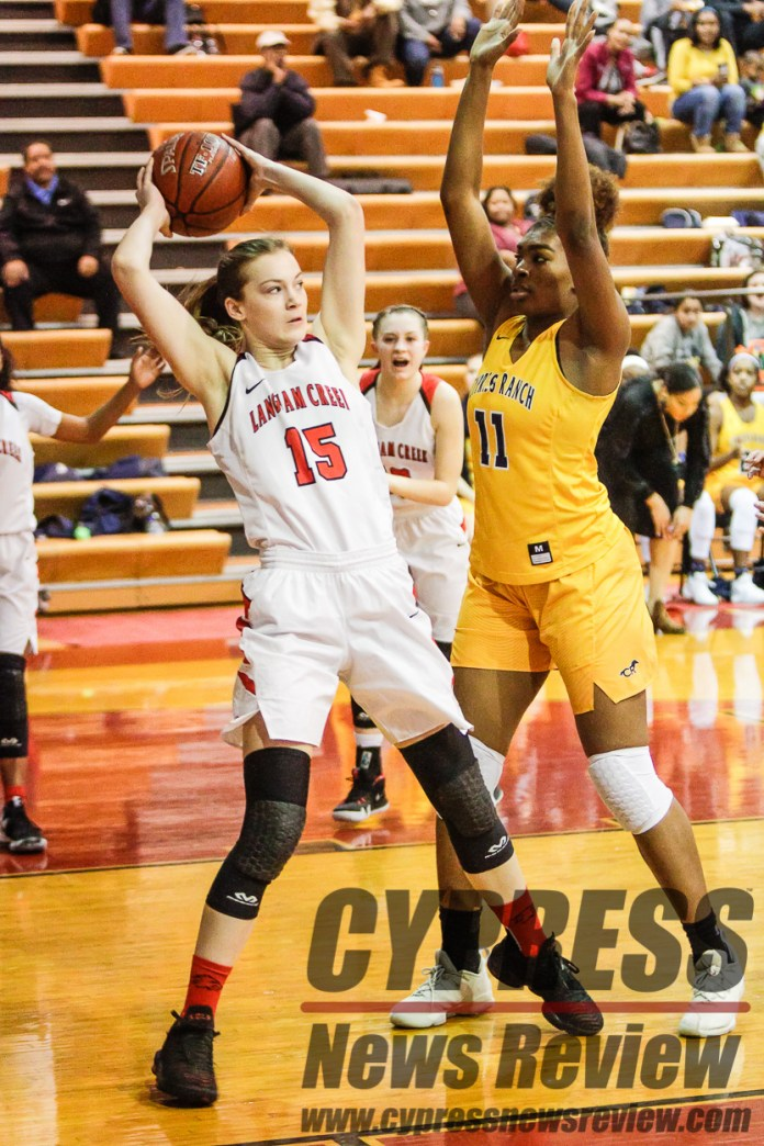 Rylie Elkin (Langham Creek 15) looks to pass, as Ki'ana Hart (Cy Ranch 11) tries to block her during the second round of league action at the Lobo gym, Jan. 15, 2019. (Cypress News Review photo by Creighton Holub)