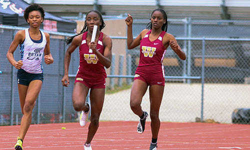 Cypress Woods High School junior Lauren Lucas (center) sprints after receiving the baton from teammate Nia Sims (right). The two, Kristen Hughes and Jordan Perry formed the team's 4x100-meter relay that qualified for the UIL Track and Field State Meet in Austin after placing second at the Region II-6A meet. Lucas also qualified for state in the 100-meter dash and long jump. (CFISD courtesy photo by Cypress Ranch HS journalism)