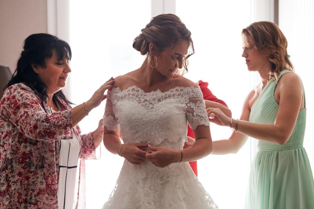 La mariée enfile sa robe aidée des sa famille