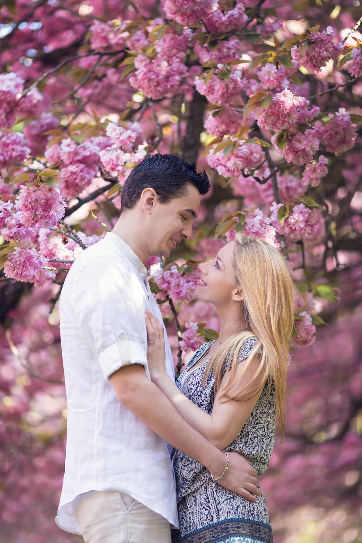 séance engagement romantique dans un parc avec les cerisiers en fleurs