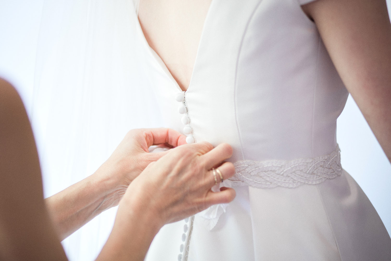 Maman qui aide sa fille à enfiler sa robe de mariée