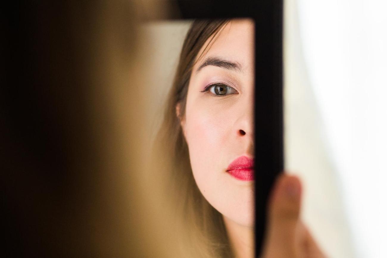 Portrait de la mariée pendant qu'elle se regarde dans un miroir