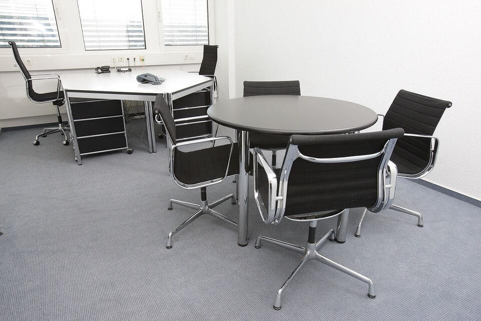 Fotografija dva uredska stola okruglog i romboidnog oblika sa pripadajućim uredskim stolicama