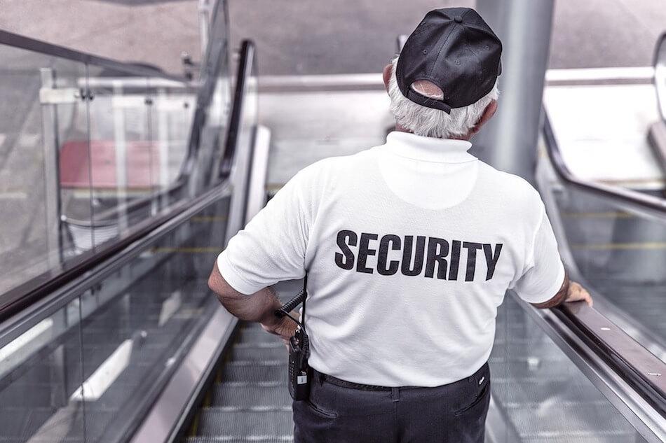 Fotografija radnika osiguranja snimljenog sa leđa na pokretnim stepenicama
