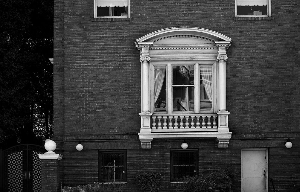 Black and white photograph of a brick mansion, with ornate stone window frame.