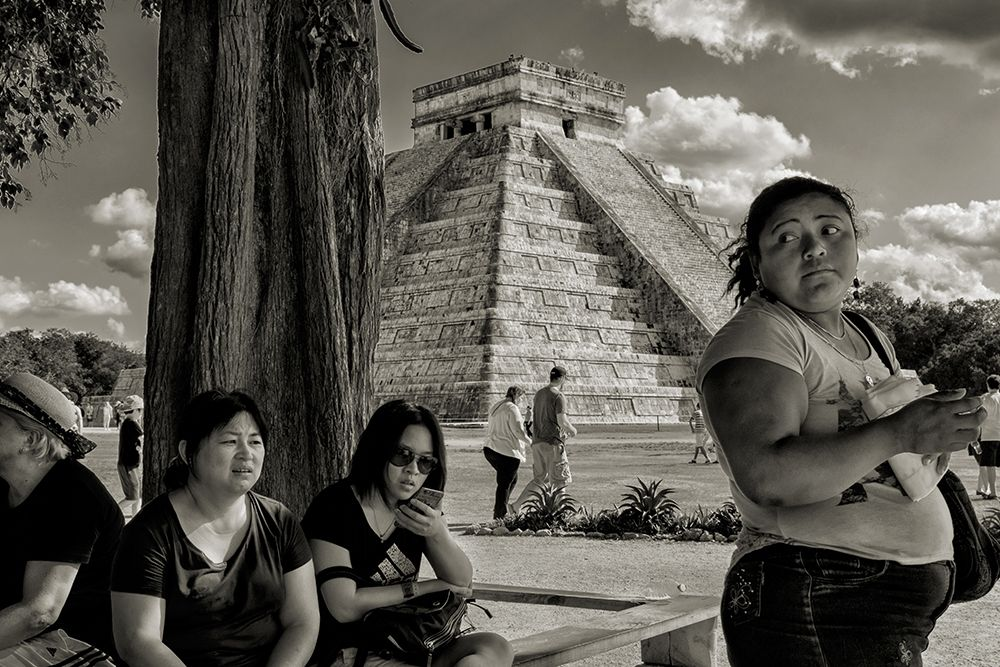 Black and white photo of people standing in the shade, with a Mayan pyramid in the background.