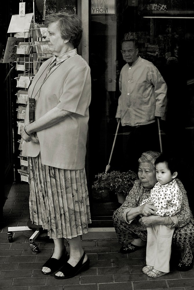 Black and white photo of a Chinese woman with a Chinese toddler, along with a Chinese man sweeping and a caucasion woman looking toward the street.