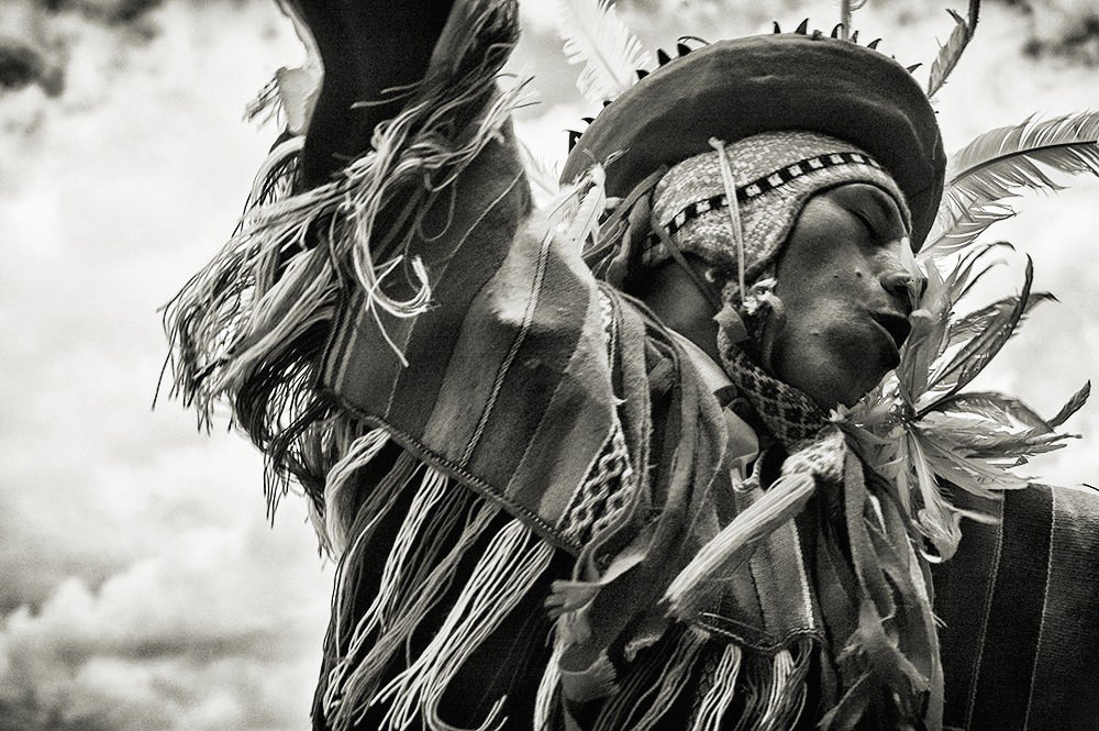 Black and white photo of an indigenous man dancing in traditional costume.