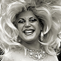 Black and white photo of a female impersonator with huge blonde hair and a diamond necklace.