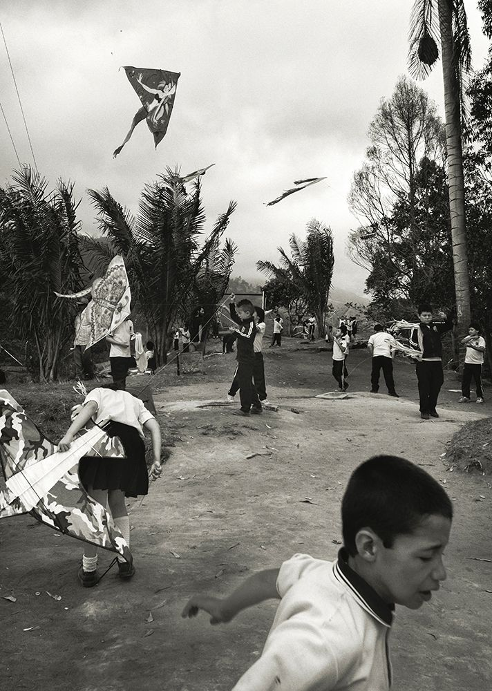 Black and white photo of kids flying kites.