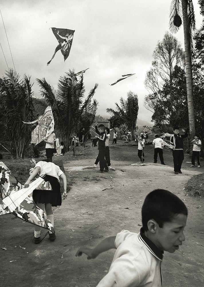 Black and white photo of kids flying kites.