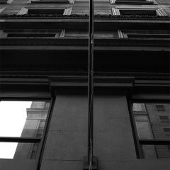 Black and white photograph looking up the side of an old brick building with a flagpole in the foreground.