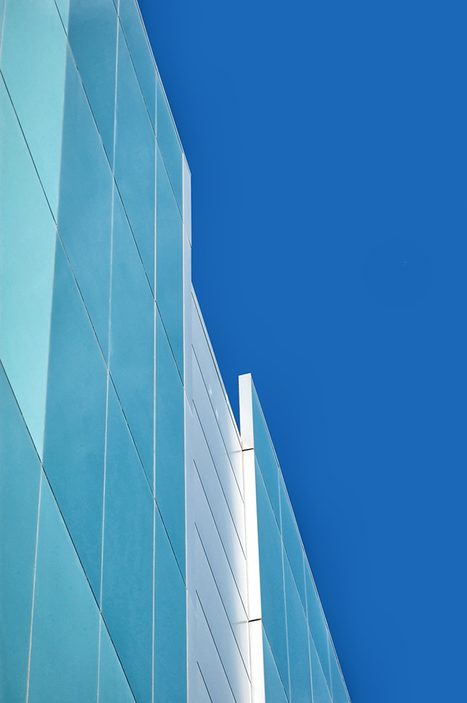Color photograph of a modern glass buidling with blue sky.