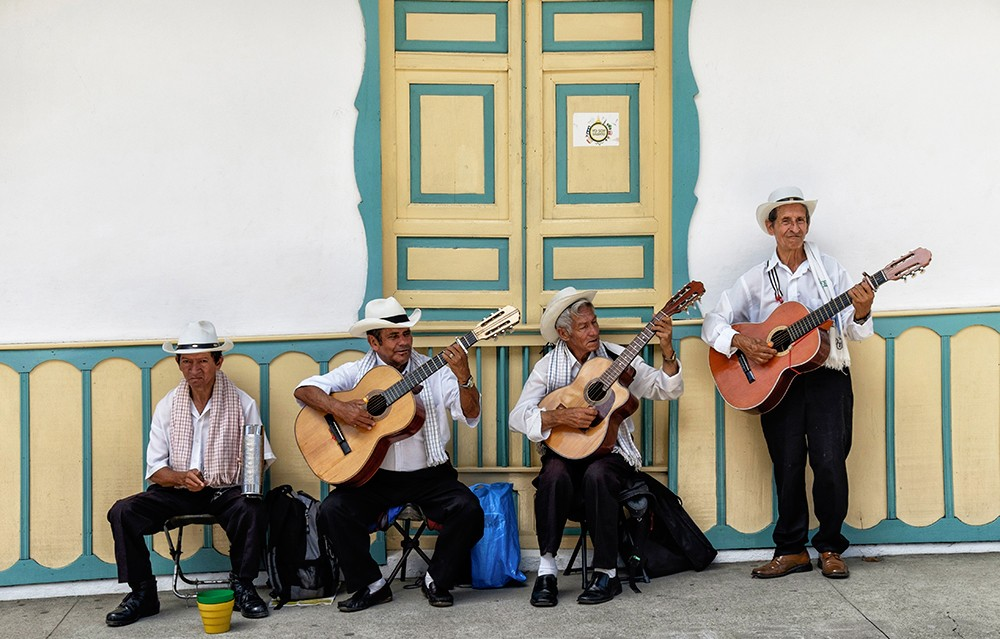 Color photo of Colombian street musicians playing guitars.