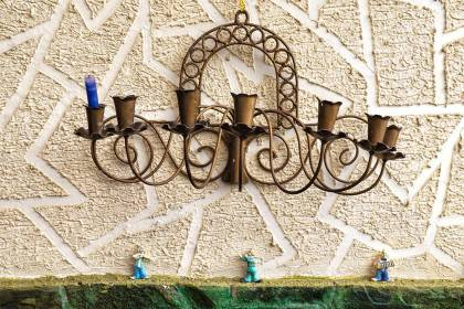 Color photo of a metal candleholder with one blue candle hanging on a textured stucco wall above tiny figurines of clown musicians.