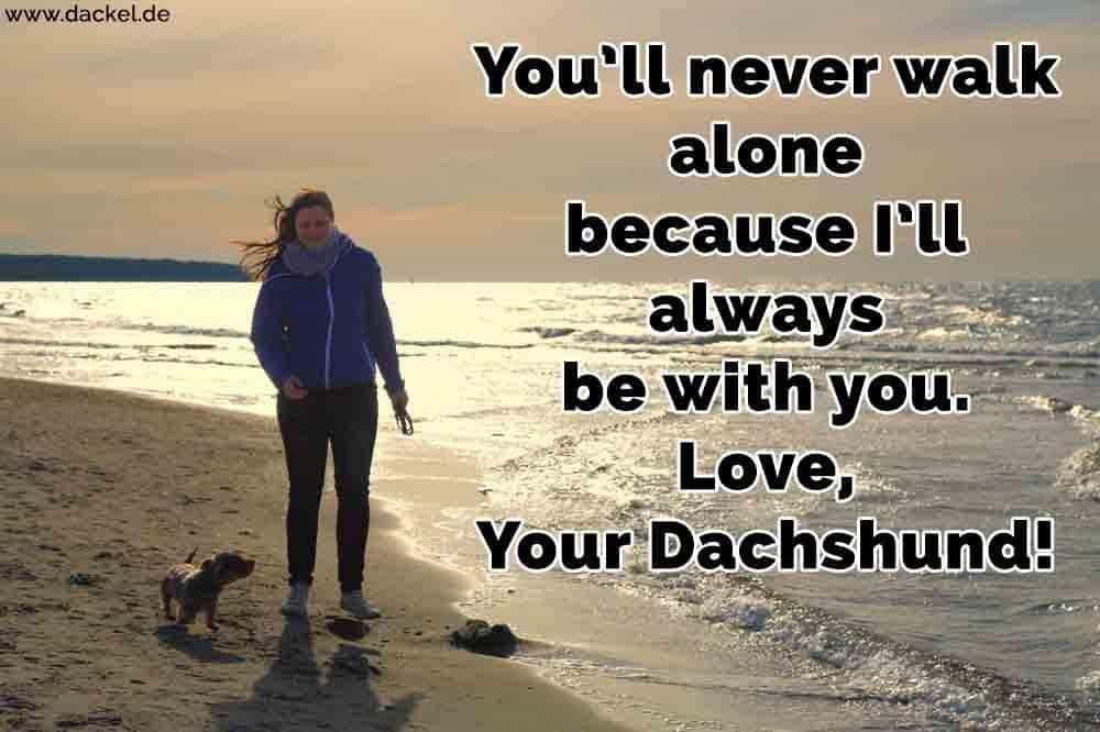 Eine Frau mit einem Dackel spazieren am Strand