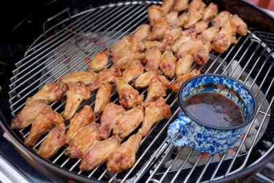 Chicken wings grilling over indirect heat while the sauce simmers over the coals